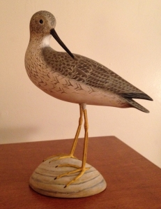 """""""Yellow Legs"""" by Christa Edlund, carved from bass wood with covered copper tubing for legs, painted with acrylics, with glass eyes, stands about 10 inches tall."""